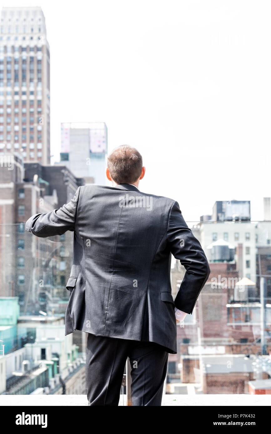 Back of young businessman standing in wrinkled business suit looking at New York City cityscape skyline in midtown Manhattan after interview break at  - Stock Image