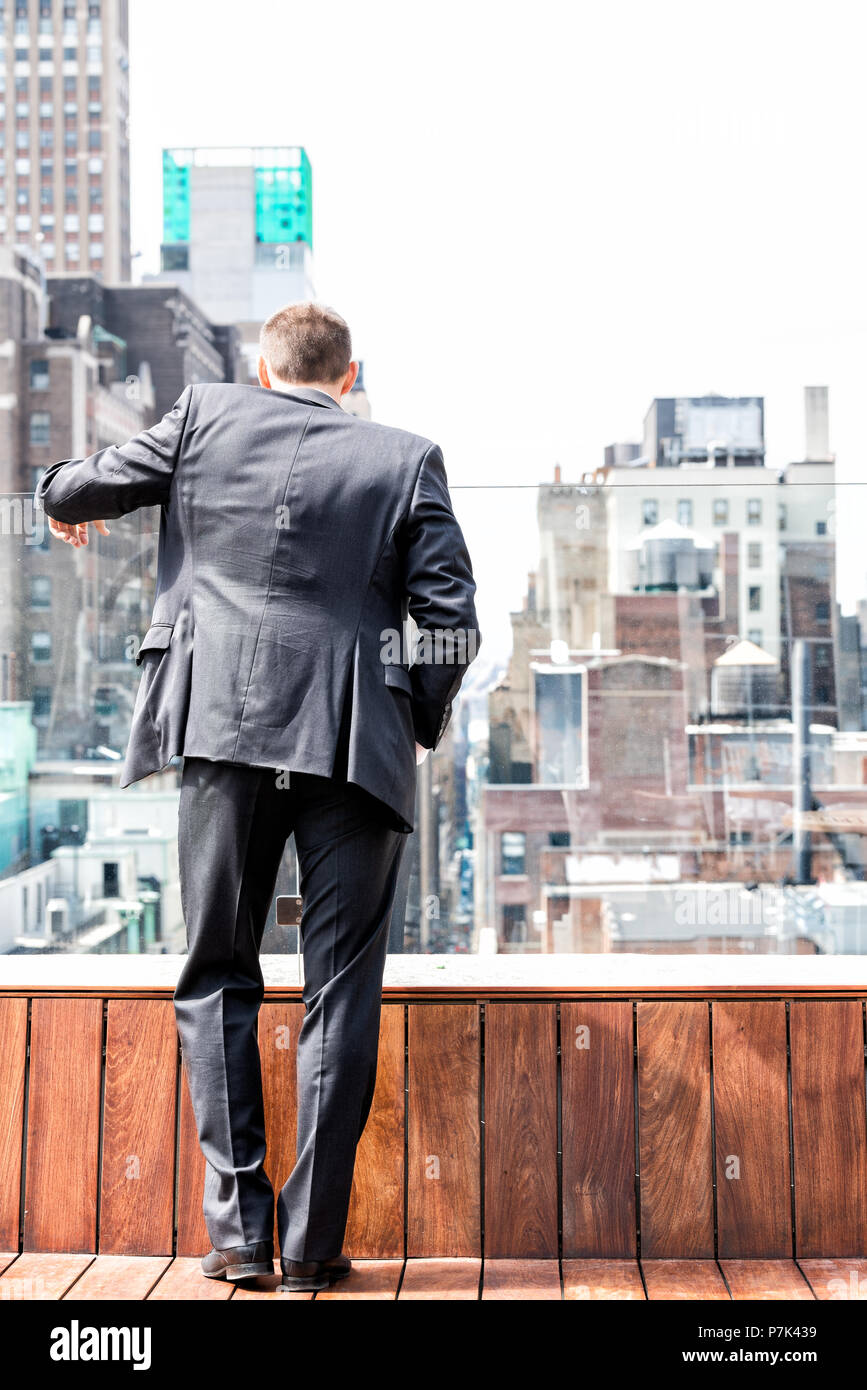Back of young businessman standing in wrinkled business suit looking down at New York City cityscape skyline in midtown Manhattan after interview brea - Stock Image