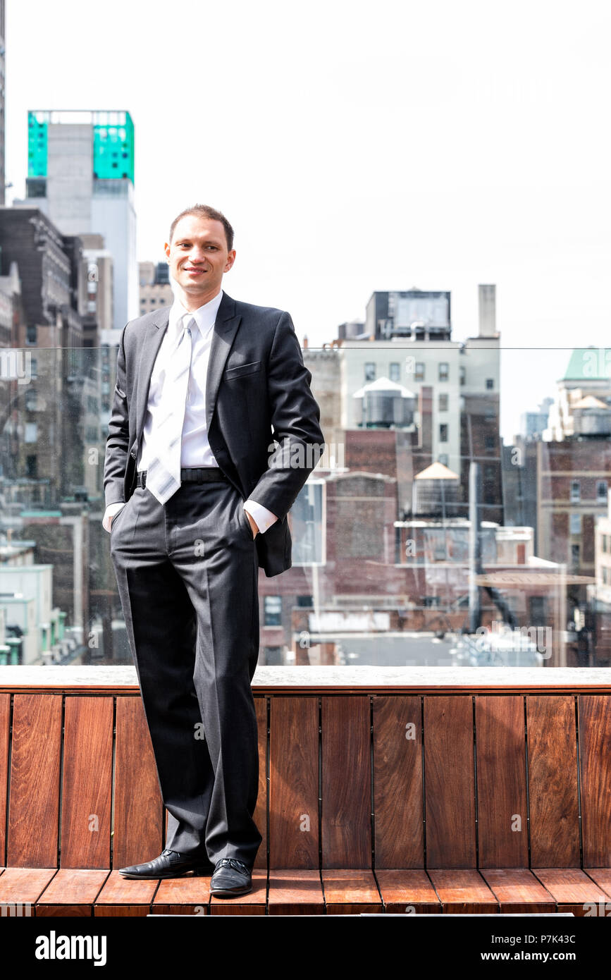Young happy smiling man businessman standing in business suit in New York City cityscape skyline in midtown Manhattan after interview, skyscrapers roo Stock Photo