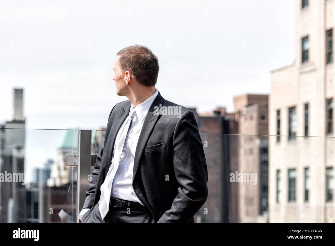 Young businessman standing in business suit looking over shoulder at New York City cityscape skyline in midtown Manhattan after interview break at sky - Stock Image