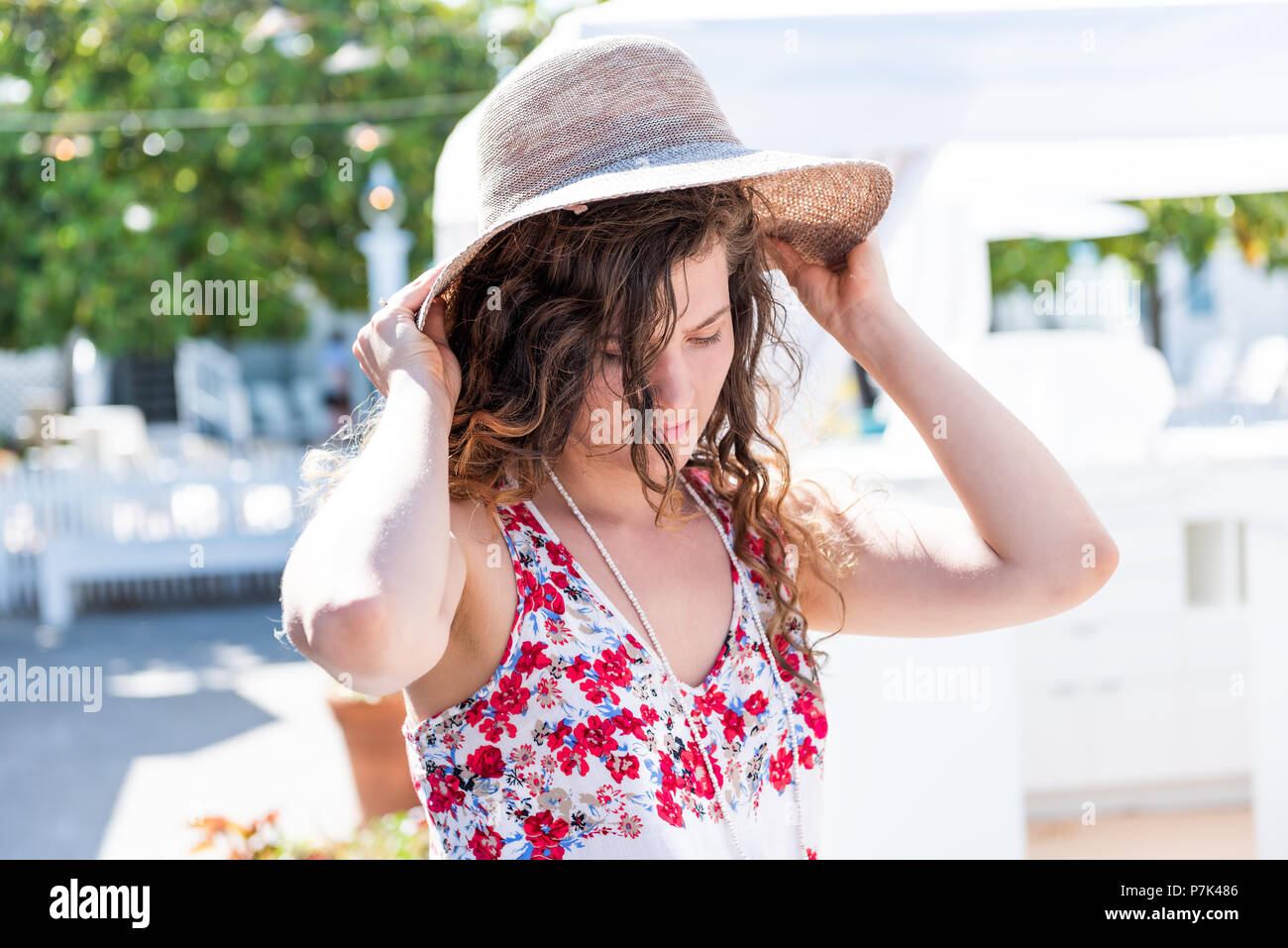Closeup of young woman shopping for straw beach hat trying on in outdoor market shop store in European, Greece, Italy, Mediterranean town, village in  - Stock Image