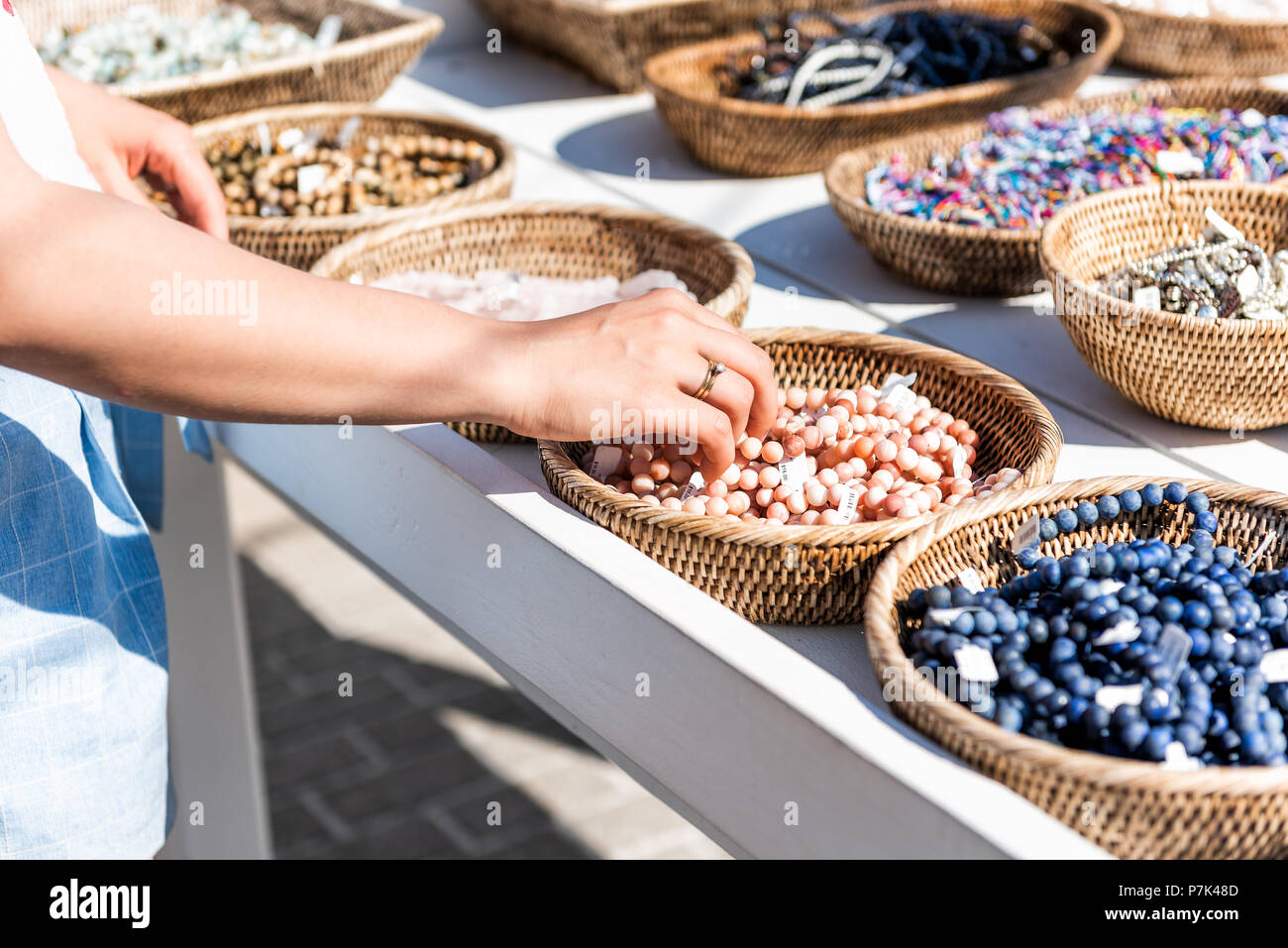 Closeup of young woman shopping for colorful stone beach bracelets touching hand in outdoor market shop store in European, Greece, Italy, Mediterranea - Stock Image