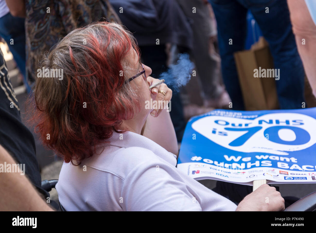 NHS 70th Anniversary March organised by People's Assembly, Woman holding a placard and smoking, London, UK, 30/06/2018 - Stock Image