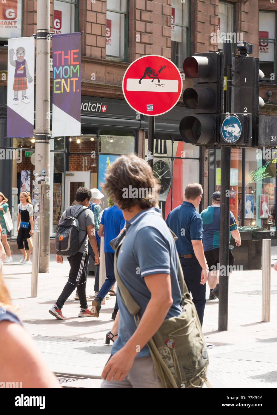 Man looking back at Clet Abraham street art road sign title 'The Clash'  on Buchanan Street, Glasgow, Scotland, UK - Stock Image