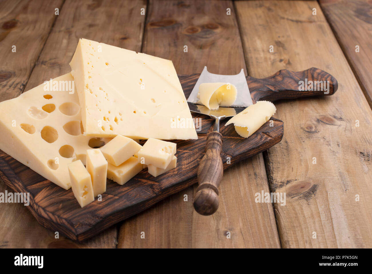 Cheese with holes large and small. Wooden board and knife. Traditional Dutch cheese. Copy space. - Stock Image