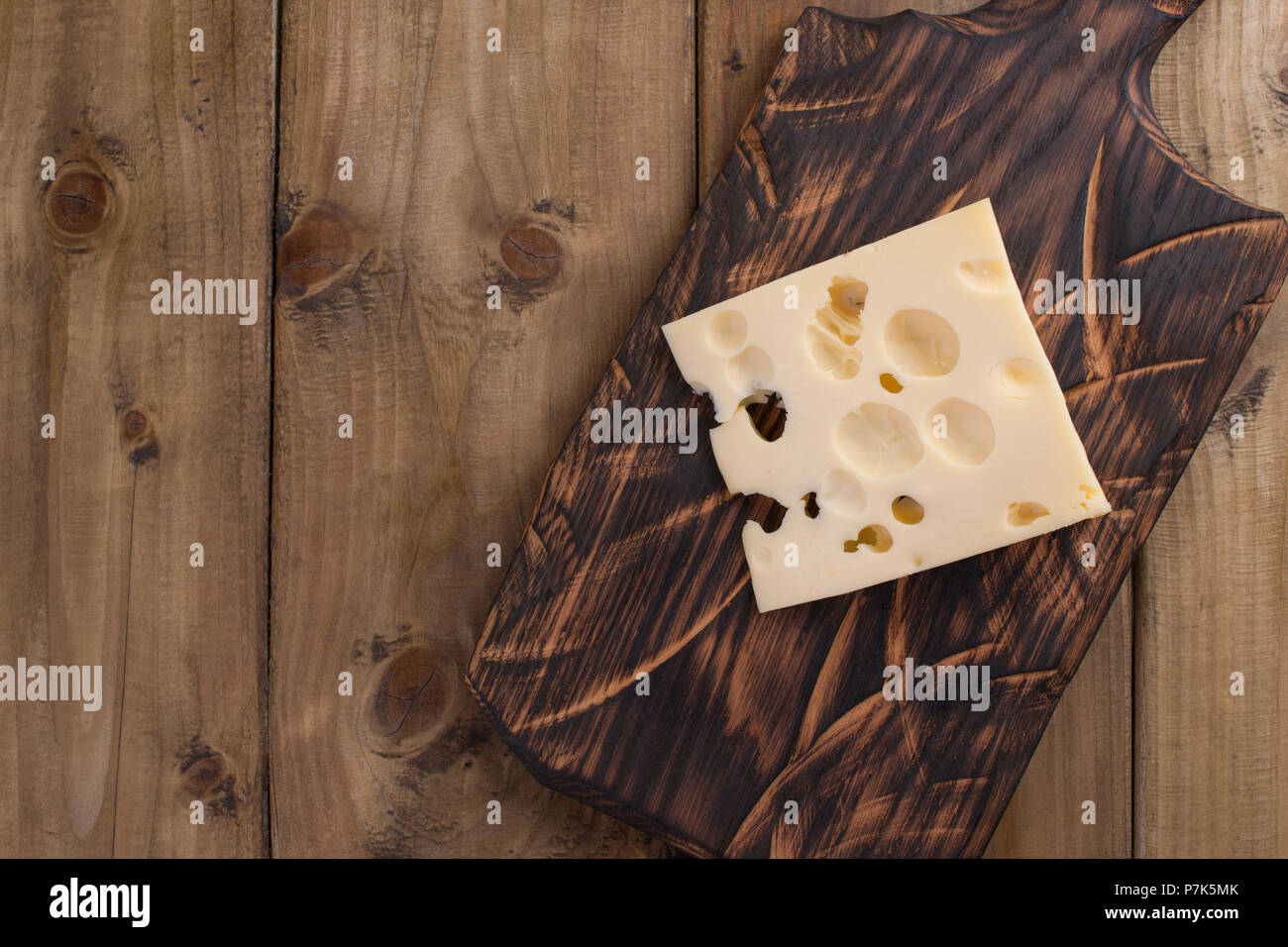 Traditional Dutch cheese with holes, on a vintage wooden board, wooden background. Dairy. Copy space. Above - Stock Image