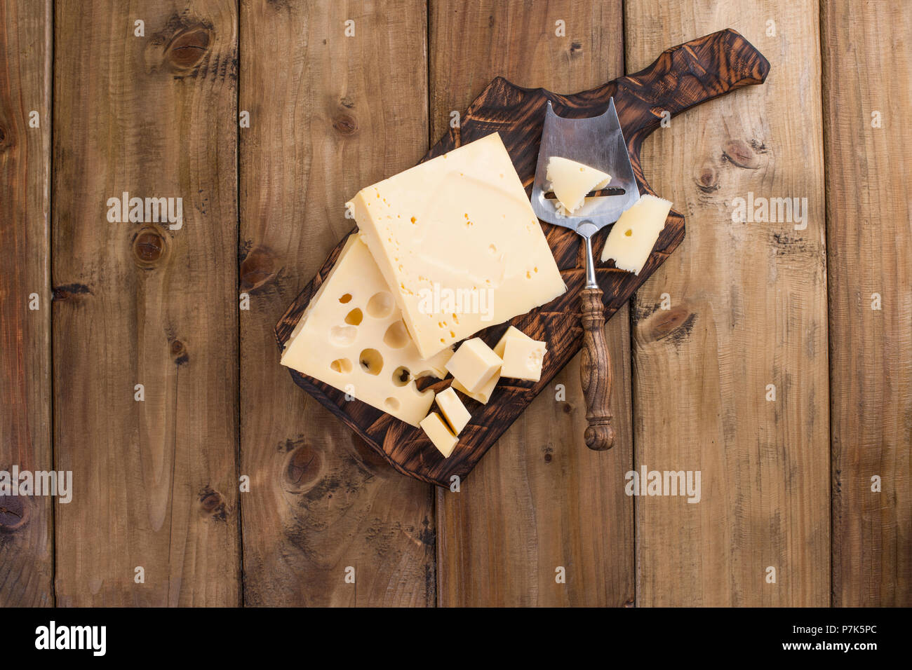 Traditional Dutch cheese with holes, on a vintage wooden board, wooden background and knife for cheese. Dairy. Copy space - Stock Image