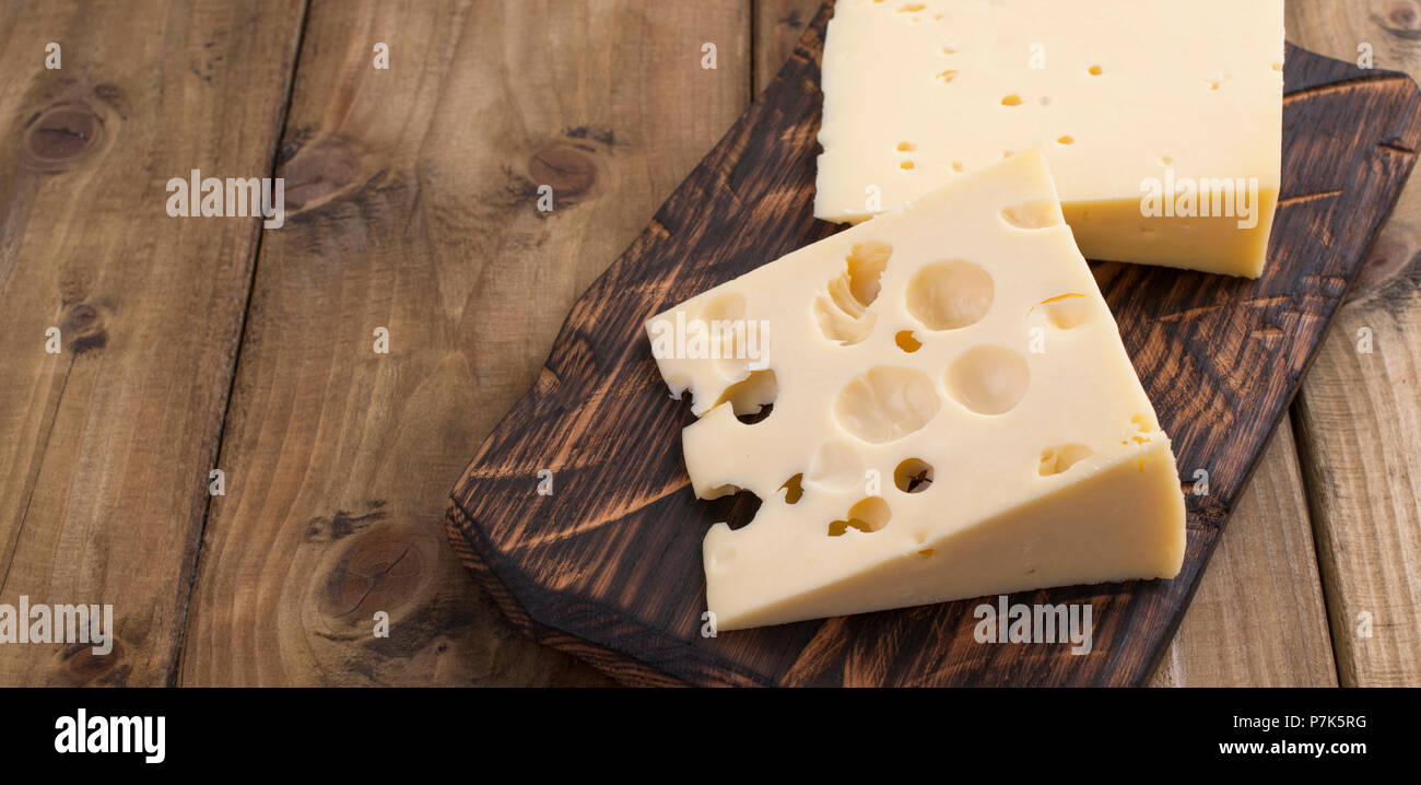 Traditional Dutch cheese with holes, on a vintage wooden board, wooden background. Dairy. Copy space. Above. Banner - Stock Image