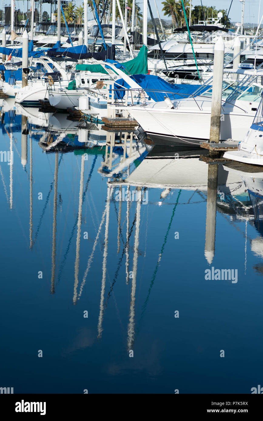 Reflections of Sailboats in the ocean marina at sunrise - Stock Image