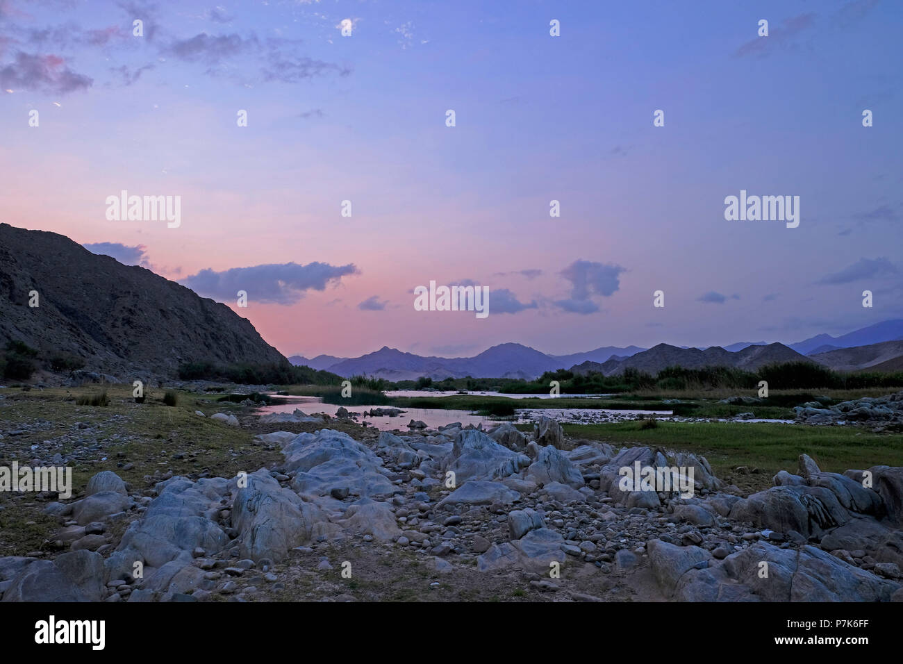 stony river bed of the Orange River / Oranjerivier (border river) in Richtersveld at evening mood, opposite side of Namibia, Namaqua, South Africa Stock Photo