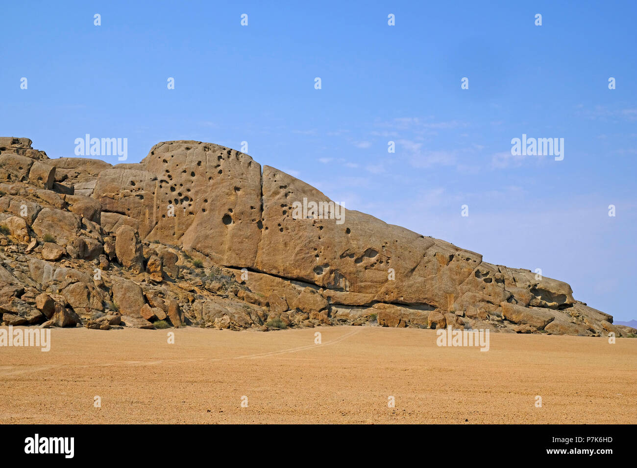 Monolith granite rocks with deep holes and crevices in the flanks in a side valley of the dry river Khumib at Skeleton Coast Park in Namibia, Kaokoland Stock Photo