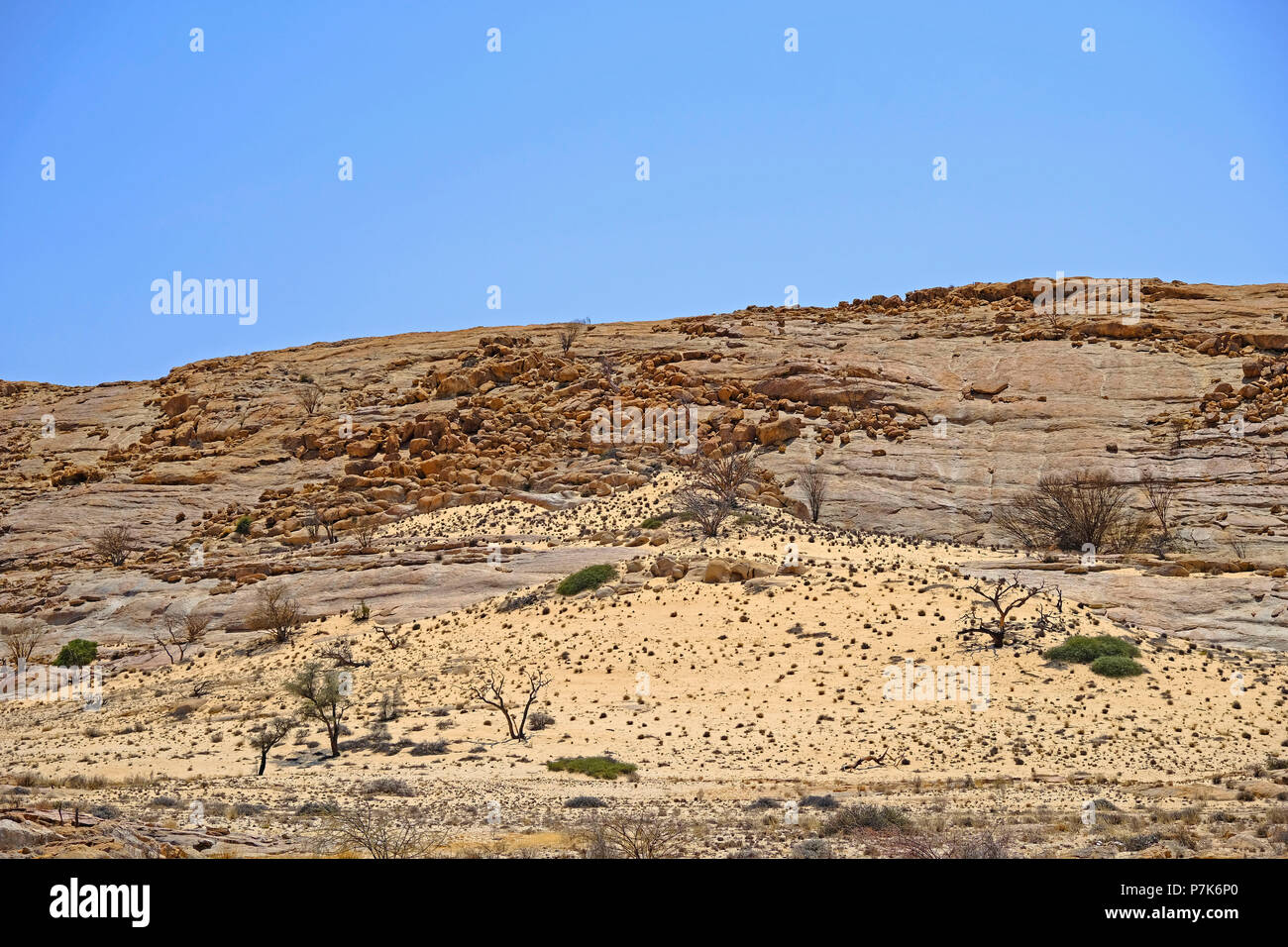 large monolith rocks with eroded granite balls, sand drifts and sparse vegetation in the Brandberg area in Namibia, Damaraland - Stock Image