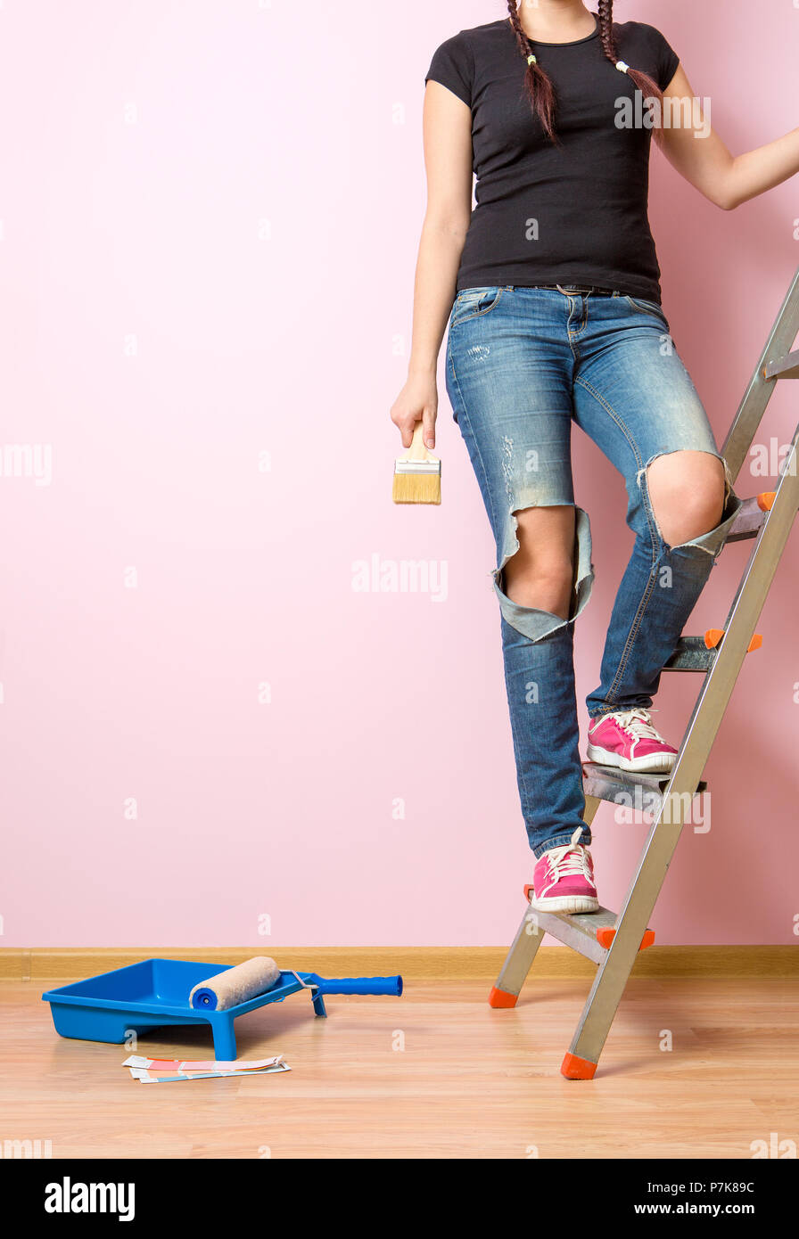 Photo woman with brush standing on stepladder Stock Photo