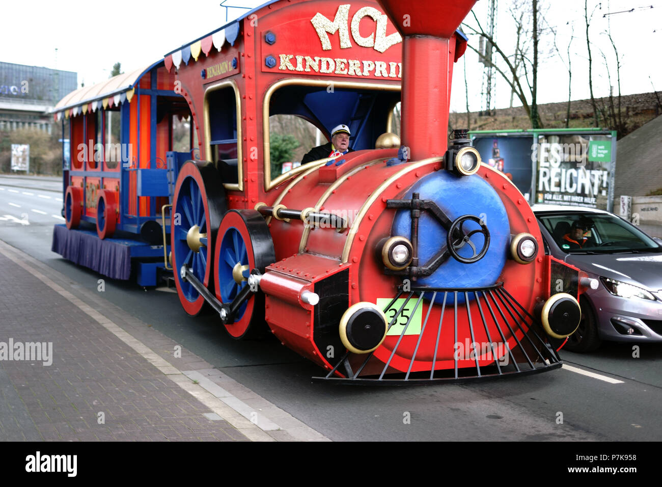 A locomotive-type vehicle with trailers for city tours driving children at carnival time in Mainz, - Stock Image