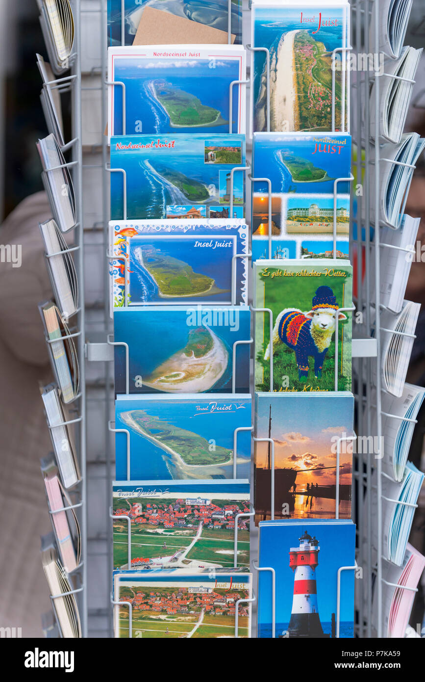 Germany, Lower Saxony, East Frisia, Juist, postcard stand in front of a souvenir shop. - Stock Image