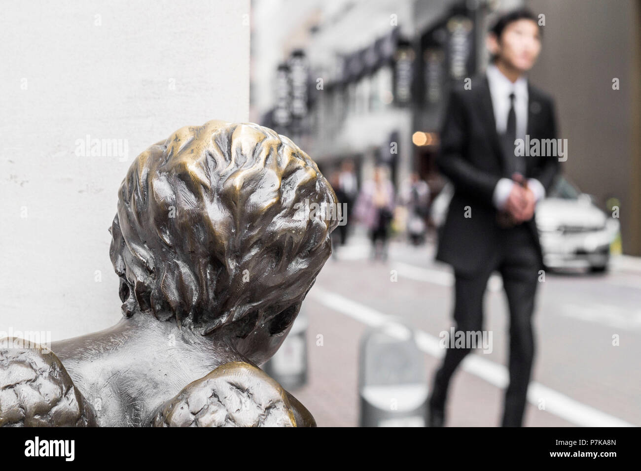 A businessman in a suit beeing watched from a statue - Stock Image