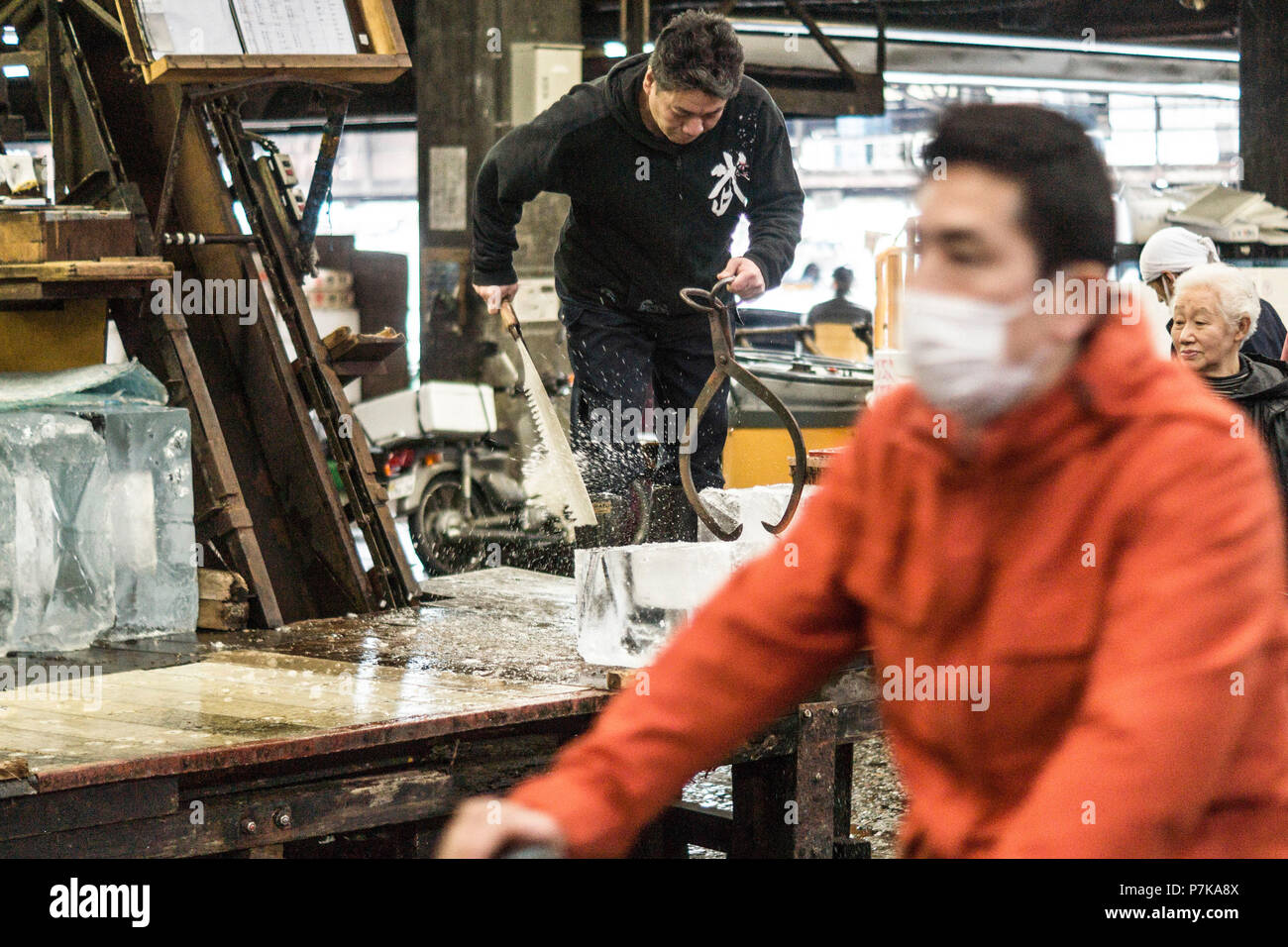 A worker at the fish market in Tokyo cuts a block of ice - Stock Image