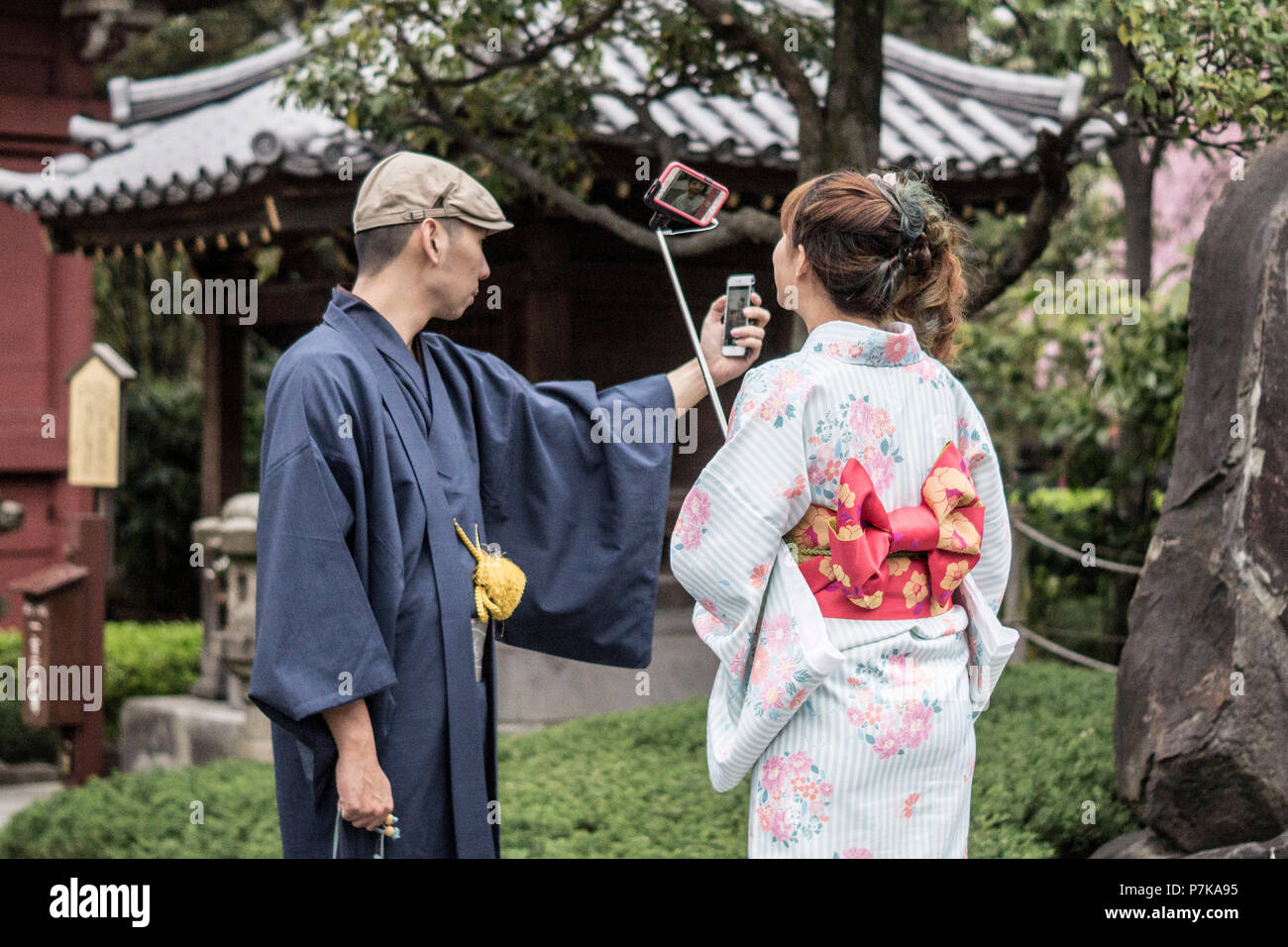 Two people taking selfies in a temple complex in Tokyo - Stock Image