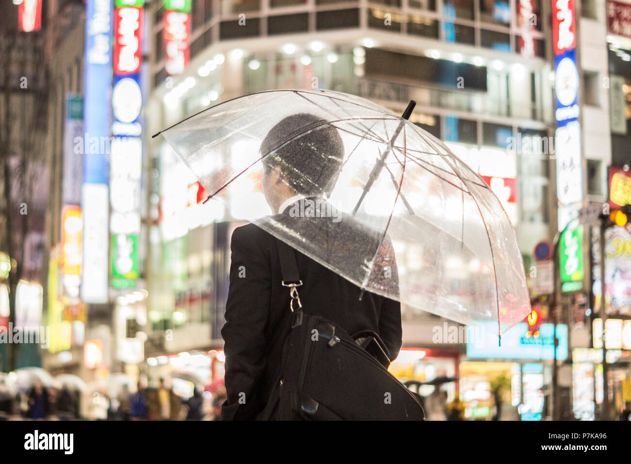 A businessman with an umbrella in the brightly lit streets in the evening - Stock Image
