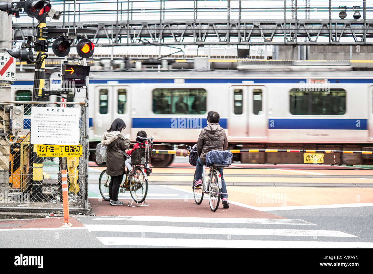 Locals in front of a railroad crossing in Tokyo - Stock Image