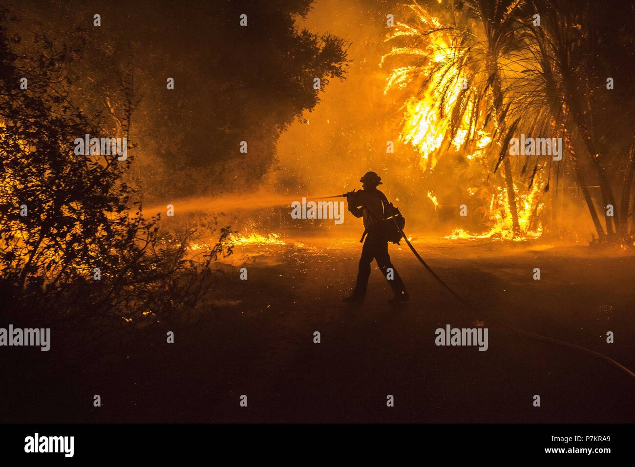 Goleta, California, USA. 6th July, 2018. A Firefighter fights the Holiday Fire north of Fairview Avenue Friday evening. Amid a record-setting heat wave in Southern California, the Holiday Fire burned up to 20 structures and 2,000 people were evacuated. Credit: Erick Madrid/ZUMA Wire/Alamy Live News - Stock Image