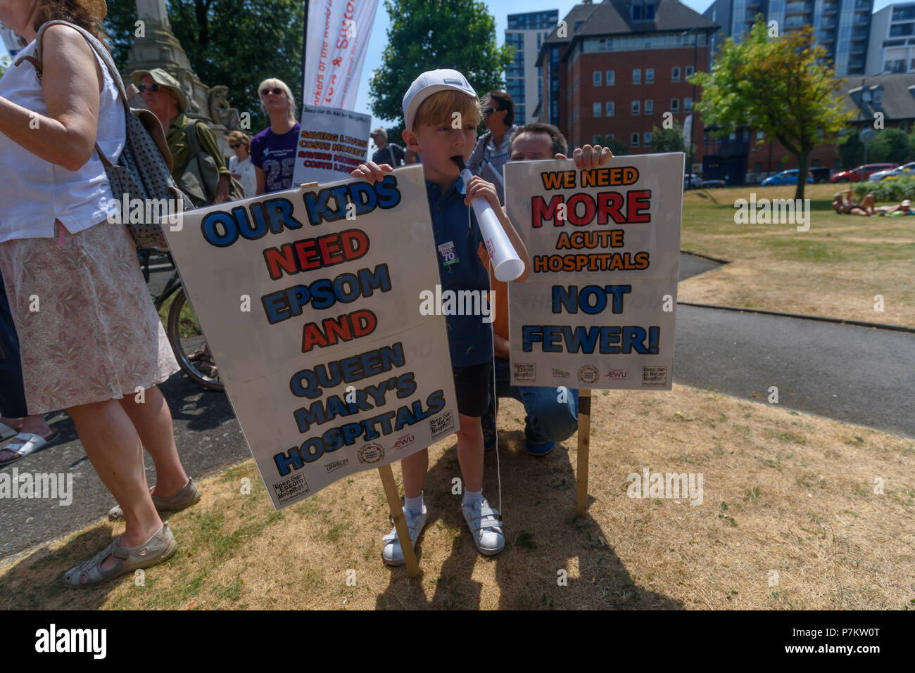 London, UK. 7th July 2018. A young supporter of the Keep Our St Helier Hospital (KOSHH) campaign against the closure of acute facilities at Epsom and St Helier Hospitals in south London blows a vuvuzela before they march to celebrate the 70th Birthday of the NHS from Sutton to a rally in front of St Helier Hospital.  The closures are prompted by government cuts which call for huge savings by Credit: Peter Marshall/Alamy Live News - Stock Image