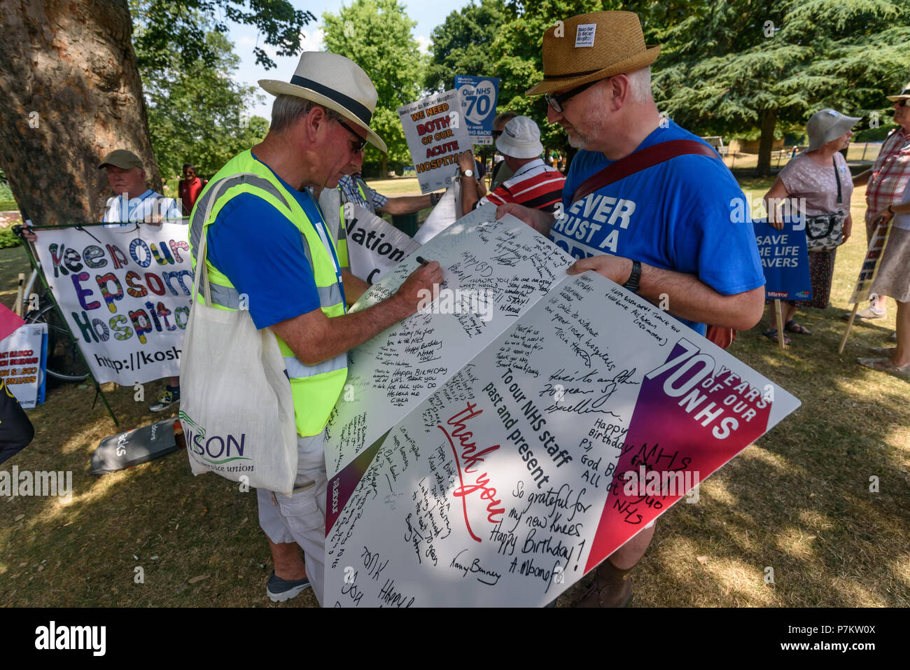 London, UK. 7th July 2018. Keep Our St Helier Hospital (KOSHH) campaigners against the closure of acute facilities at Epsom and St Helier Hospitals in south London sign a card for the 70th Birthday of the NHS before marching from Sutton to a rally in front of St Helier Hospital. The Epsom and St Helier Trust want to close A&E, Maternity, Paediatrics, Emergency Medicine and Surgery, Intensive Care, Coronary Care and the Cancer Centre at one or both hospitals and sell off the sites. Credit: Peter Marshall/Alamy Live News - Stock Image
