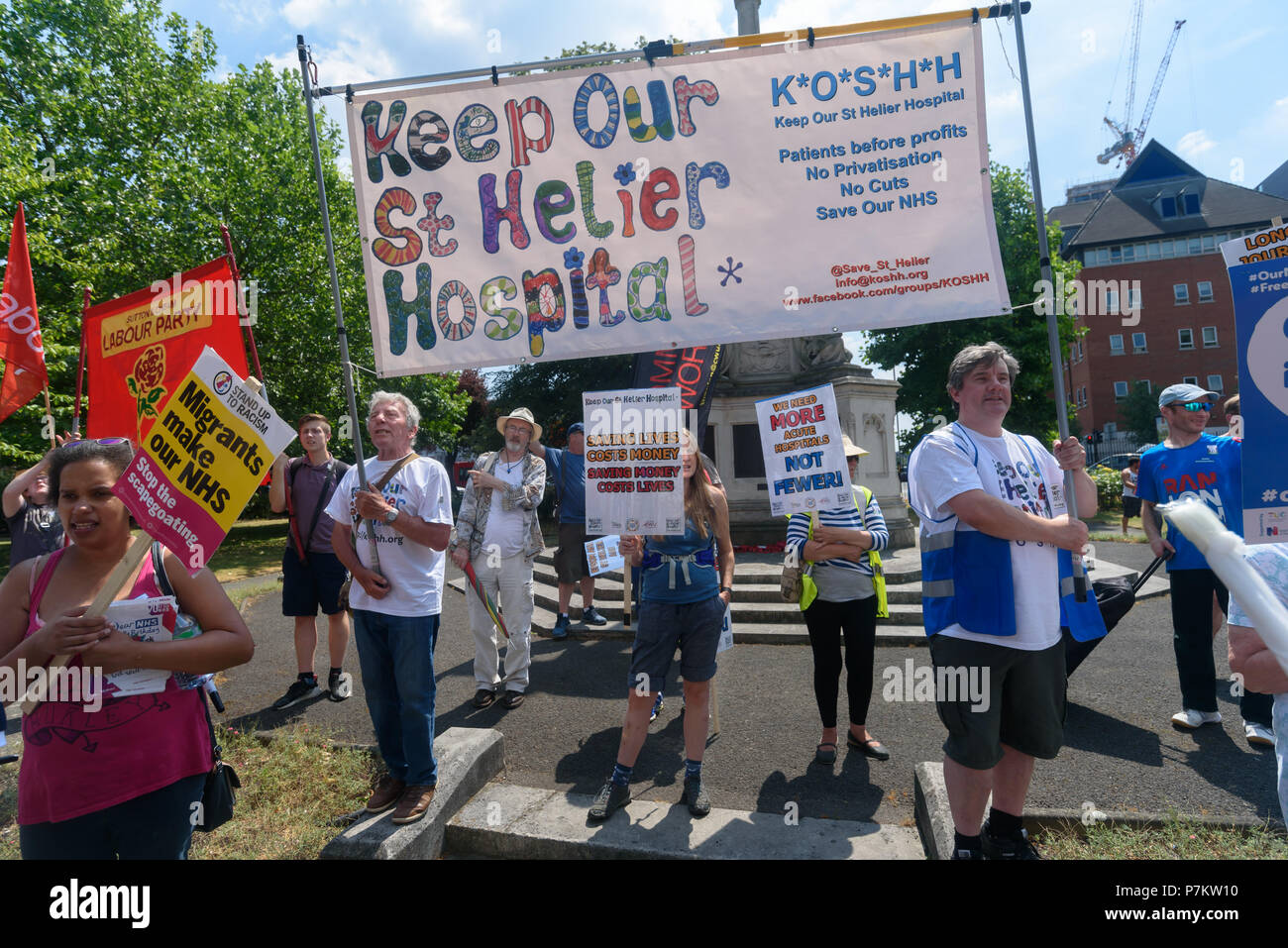 London, UK. 7th July 2018. Keep Our St Helier Hospital (KOSHH) campaigners against the closure of acute facilities at Epsom and St Helier Hospitals in south London pose before their march to celebrate the 70th Birthday of the NHS with a march from Sutton to a rally in front of St Helier Hospital.  The closures are prompted by government cuts which call for huge savings by the trust, and would Credit: Peter Marshall/Alamy Live NewsStock Photo