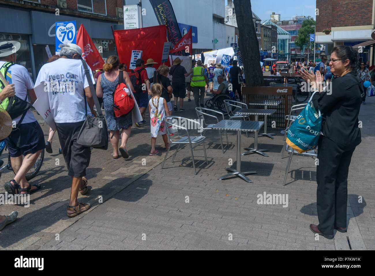 London, UK. 7th July 2018. A woman claps as Keep Our St Helier Hospital (KOSHH) campaigners against the closure of acute facilities at Epsom and St Helier Hospitals in south London celebrate the 70th Birthday of the NHS by marching from Sutton to a rally in front of St Helier Hospital.  The closures are prompted by government cuts which call for huge savings by the trust, and would leave a wi Credit: Peter Marshall/Alamy Live News Stock Photo