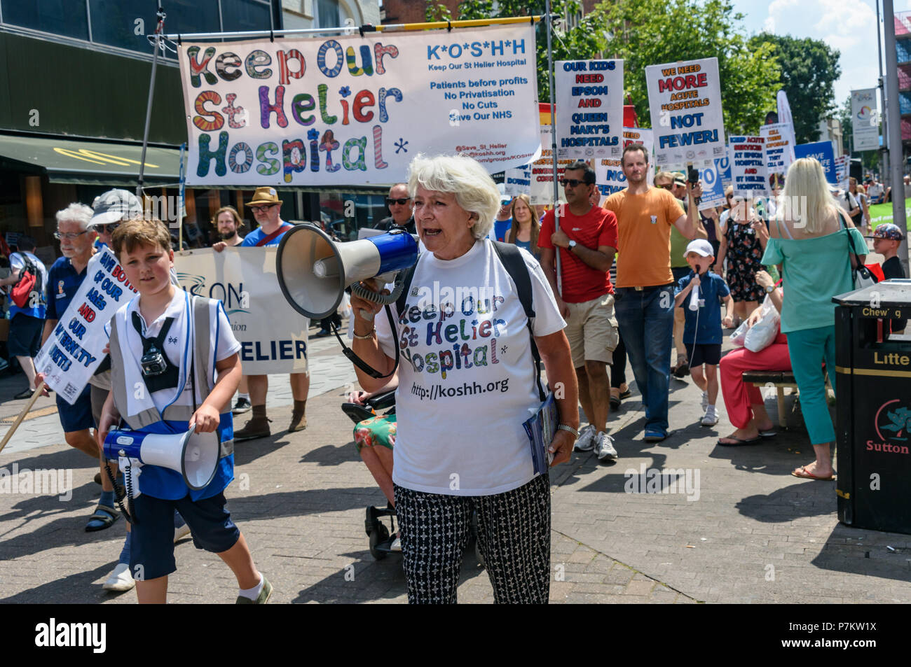 London, UK. 7th July 2018. Sandra Ash leads Keep Our St Helier Hospital (KOSHH) campaigners against the closure of acute facilities at Epsom and St Helier Hospitals in south London celebrating the 70th Birthday of the NHS by marching from Sutton to a rally in front of St Helier Hospital.  The closures are prompted by government cuts which call for huge savings by the trust, and would leave a Credit: Peter Marshall/Alamy Live News Stock Photo