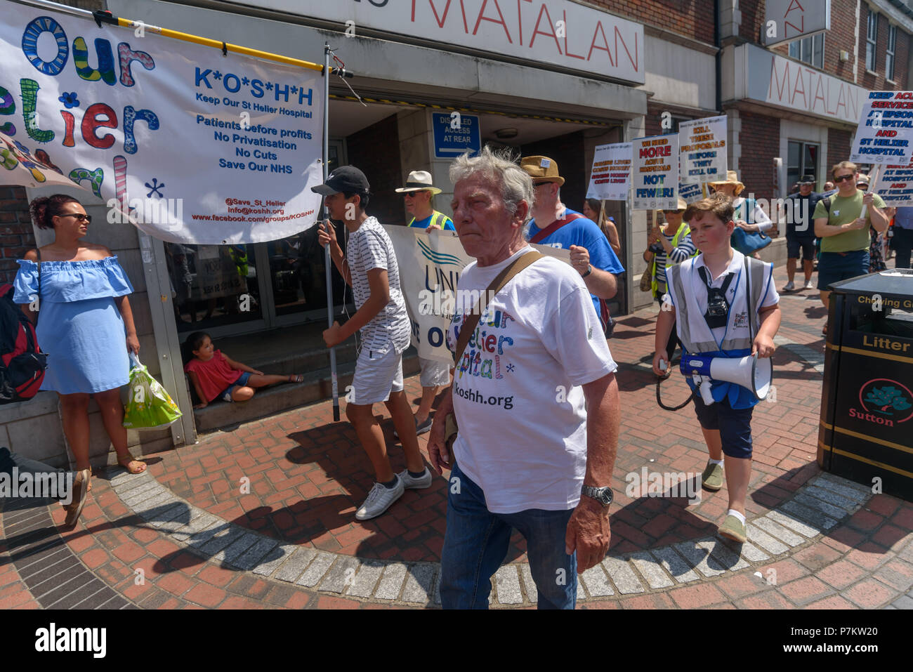 London, UK. 7th July 2018. Keep Our St Helier Hospital (KOSHH) campaigners against the closure of acute facilities at Epsom and St Helier Hospitals in south London celebrate the 70th Birthday of the NHS by marching from Manor Park through Sutton High St to a rally in front of St Helier Hospital.  The closures are prompted by government cuts which call for huge savings by the trust, and would Credit: Peter Marshall/Alamy Live NewsStock Photo