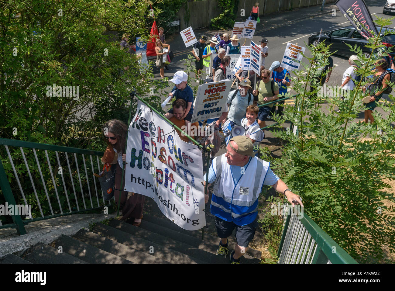 London, UK. 7th July 2018. Keep Our St Helier Hospital (KOSHH) campaigners against the closure of acute facilities at Epsom and St Helier Hospitals in south London cross a footbrindge on their march to celebrate the 70th Birthday of the NHS from Sutton to a rally in front of St Helier Hospital.  The closures are prompted by government cuts which call for huge savings by the trust, and would l Credit: Peter Marshall/Alamy Live NewsStock Photo