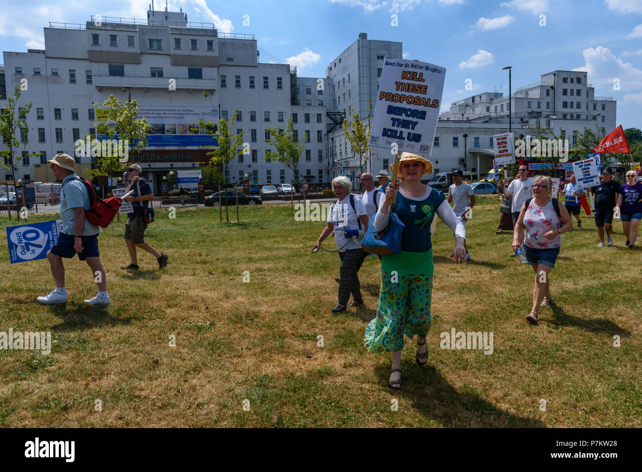 London, UK. 7th July 2018. Keep Our St Helier Hospital (KOSHH) campaigners against the closure of acute facilities at Epsom and St Helier Hospitals in south London celebrating the 70th Birthday of the NHS with a march from Sutton arrive in front of St Helier Hospital for a rally.  The closures are prompted by government cuts which call for huge savings by the trust, and would leave a wide swa Credit: Peter Marshall/Alamy Live News Stock Photo