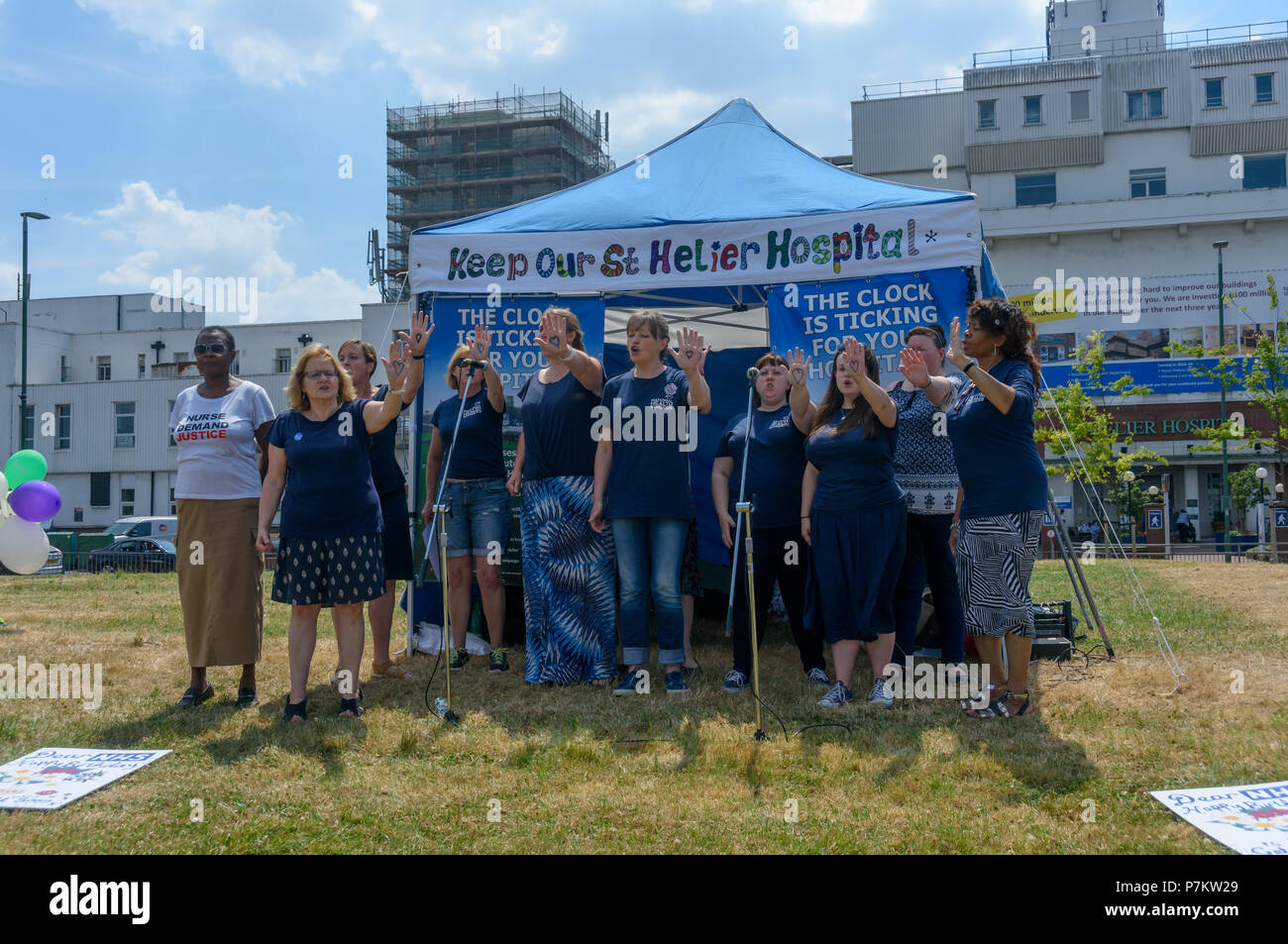 London, UK. 7th July 2018. The National Health SIngers greet the Keep Our St Helier Hospital (KOSHH) campaigners against the closure of acute facilities at Epsom and St Helier Hospitals in south London celebrating the 70th Birthday of the NHS who have marched from Sutton for a rally in front of St Helier Hospital.  The closures are prompted by government cuts which call for huge savings by th Credit: Peter Marshall/Alamy Live News - Stock Image
