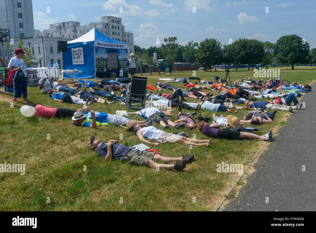 London, UK. 7th July 2018.  People take part in a short i'die-in' at the end of the march by Keep Our St Helier Hospital (KOSHH) campaigners against the closure of acute facilities at Epsom and St Helier Hospitals in south Londonl. They had marched from Sutton to a rally there celebrating the 70th birthday of the NHS and opposing hospital closures. Credit: Peter Marshall/Alamy Live NewsStock Photo