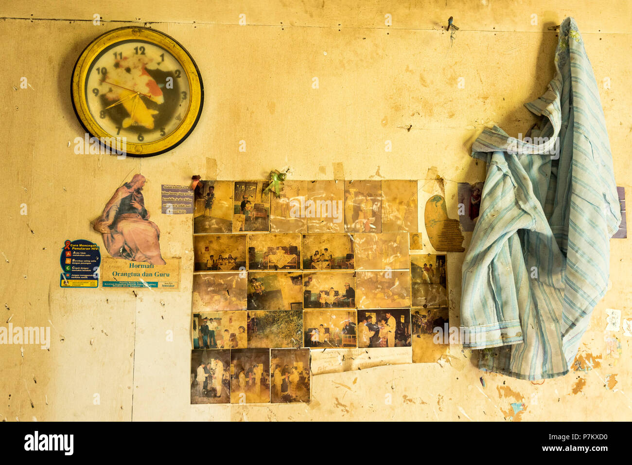 A room wall with family photos, a clock, shirt and religious portrait in an abandoned house in the red zone at the volcano Mt. Sinabung on Sumatra, Indonesia, - Stock Image