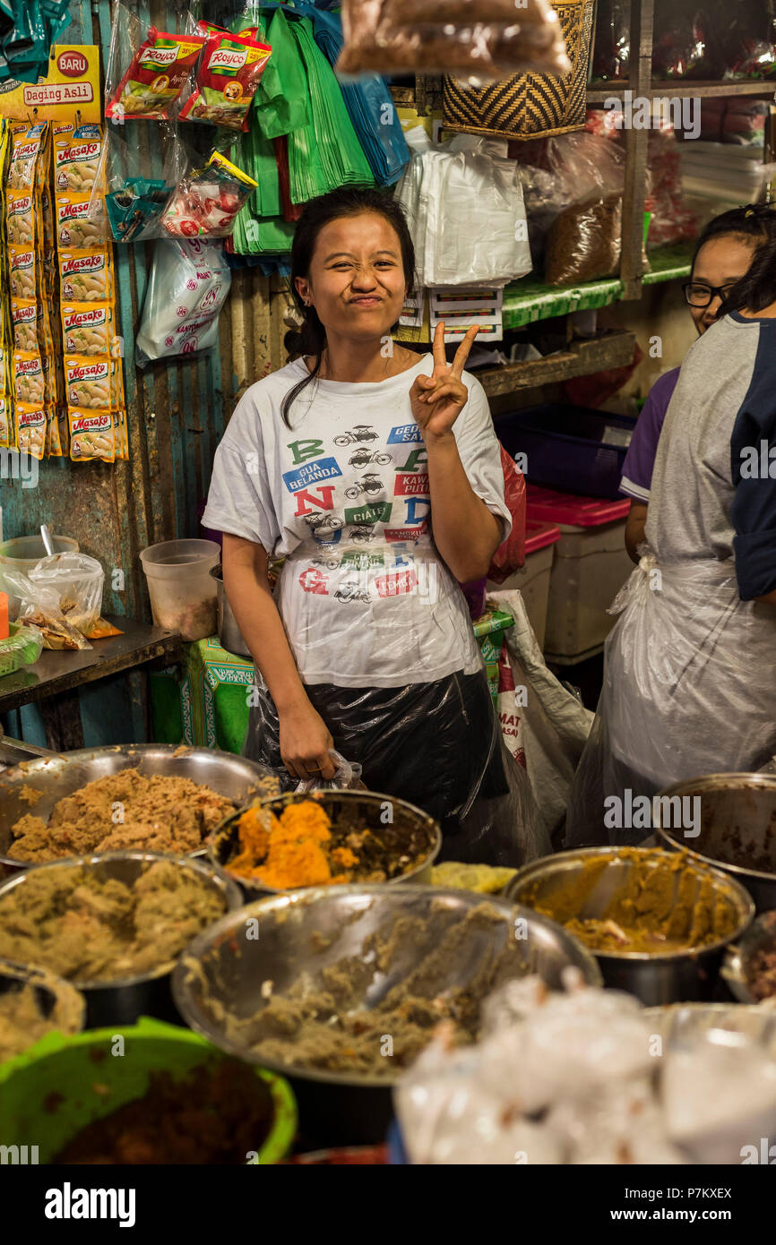 A young market trader grimacing at the camera, standing with plastic apron behind her food stand on the market of Kutacane, Indonesia - Stock Image