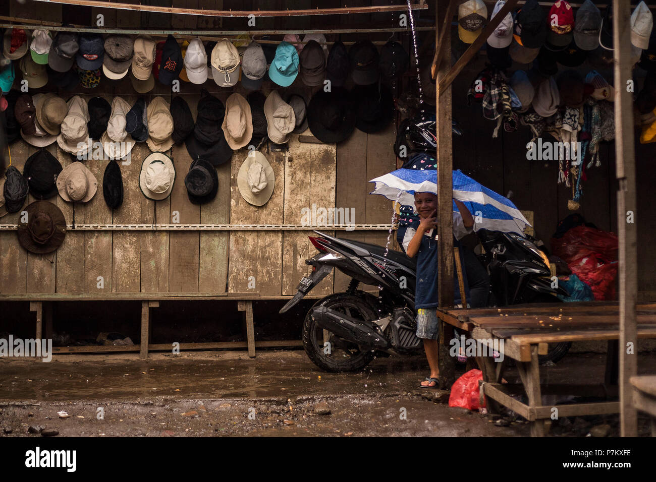 A boy with umbrella in the market square of Kutacane, Stock Photo
