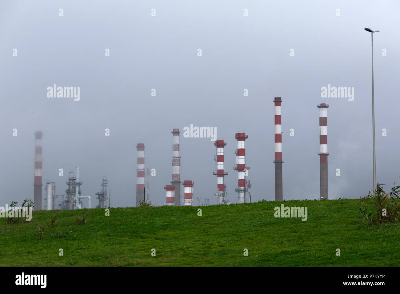 Oil refinery and powerplant chimneys between smog - Stock Image