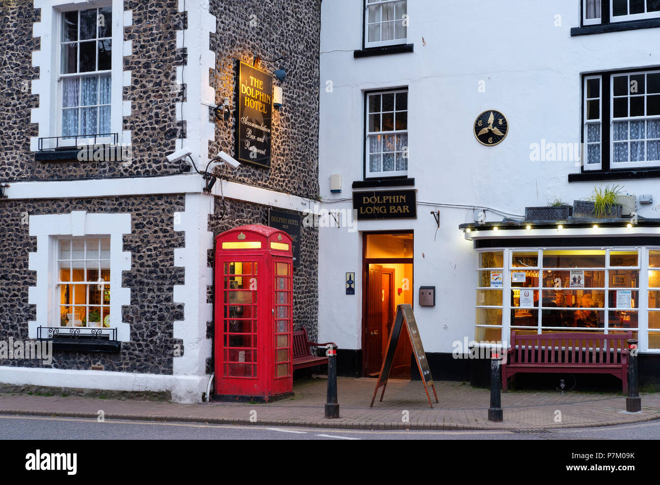 red telephone booth in front of The Dolphin Hotel, Beer, Devon, England, UK - Stock Image