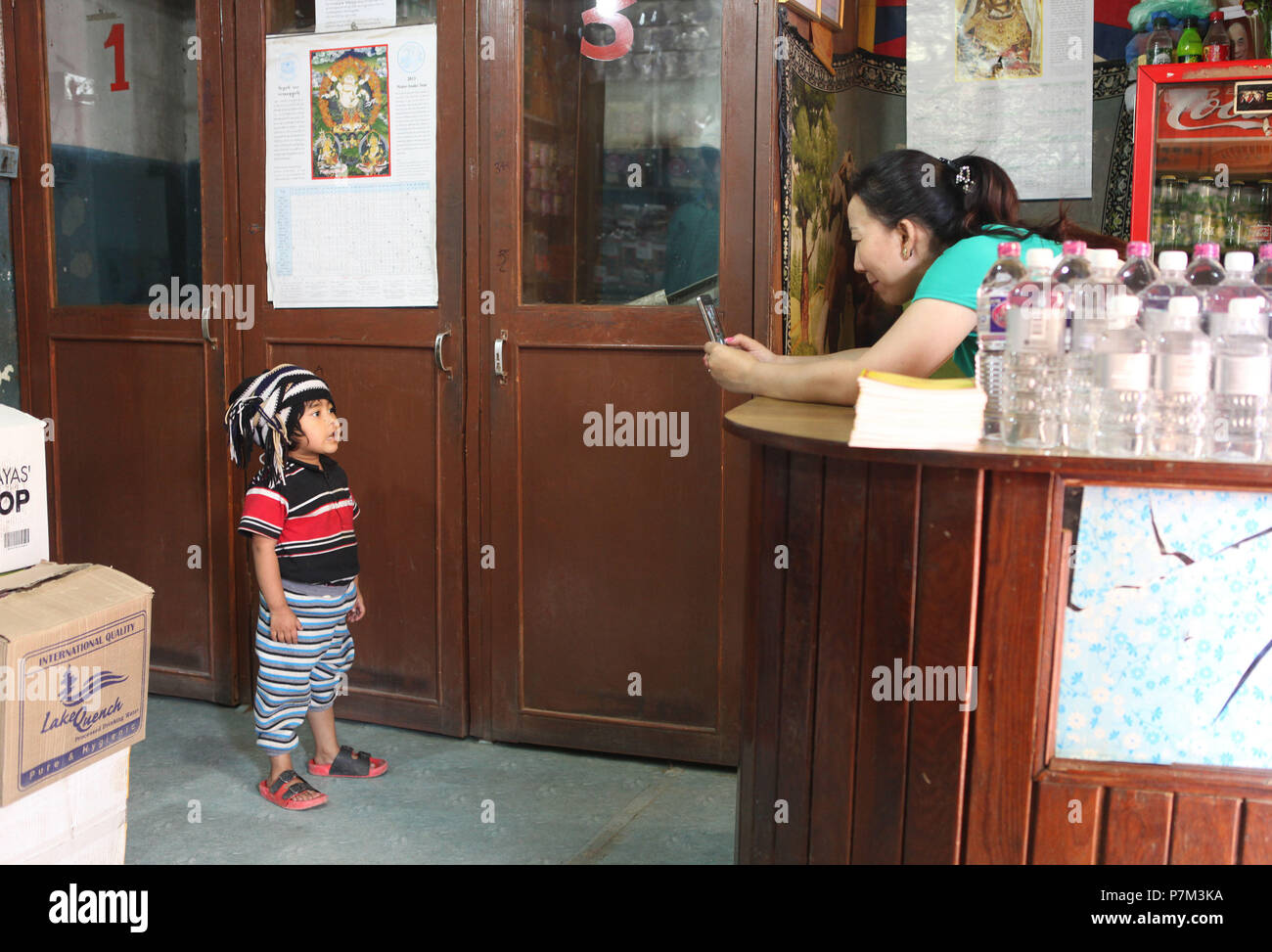Shop assistant photographing little boy with headgear in corner shop, Kathmandu, Nepal - Stock Image