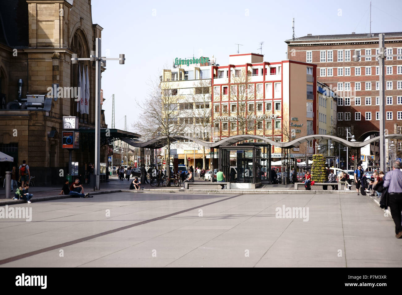 Travelers and passers-by sitting at the station forecourt in Koblenz in front of the main station in good weather. - Stock Image
