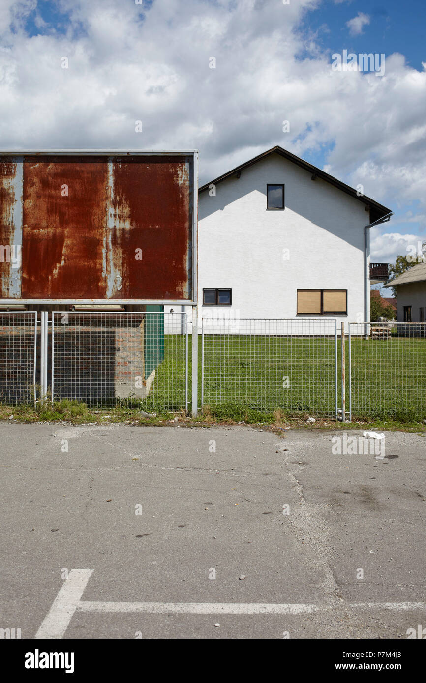Empty billboard in front of house - Stock Image