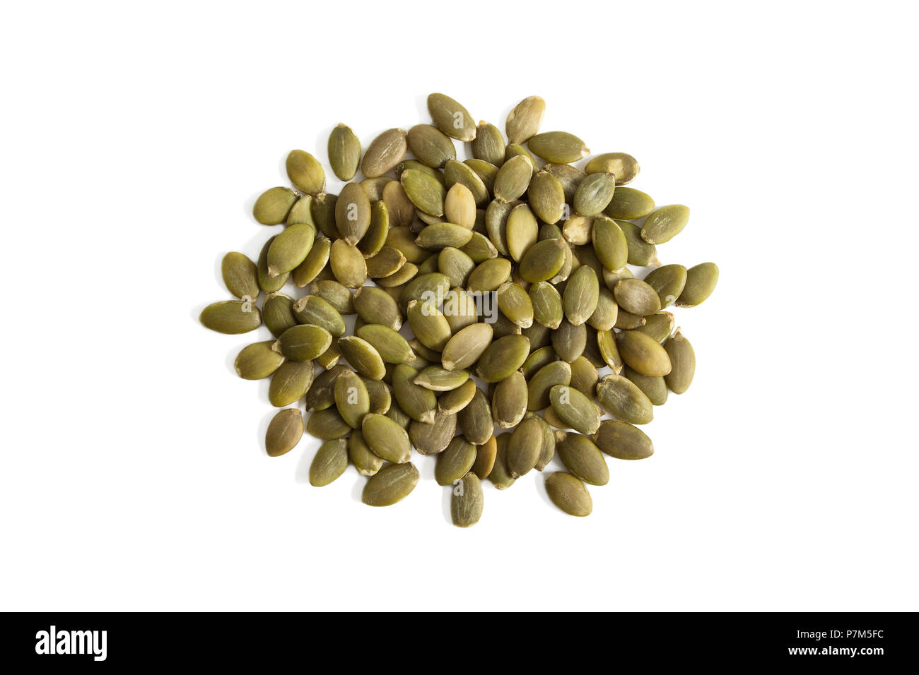 Isolated uncooked green pumpkin seeds on a white background from above. Stock Photo