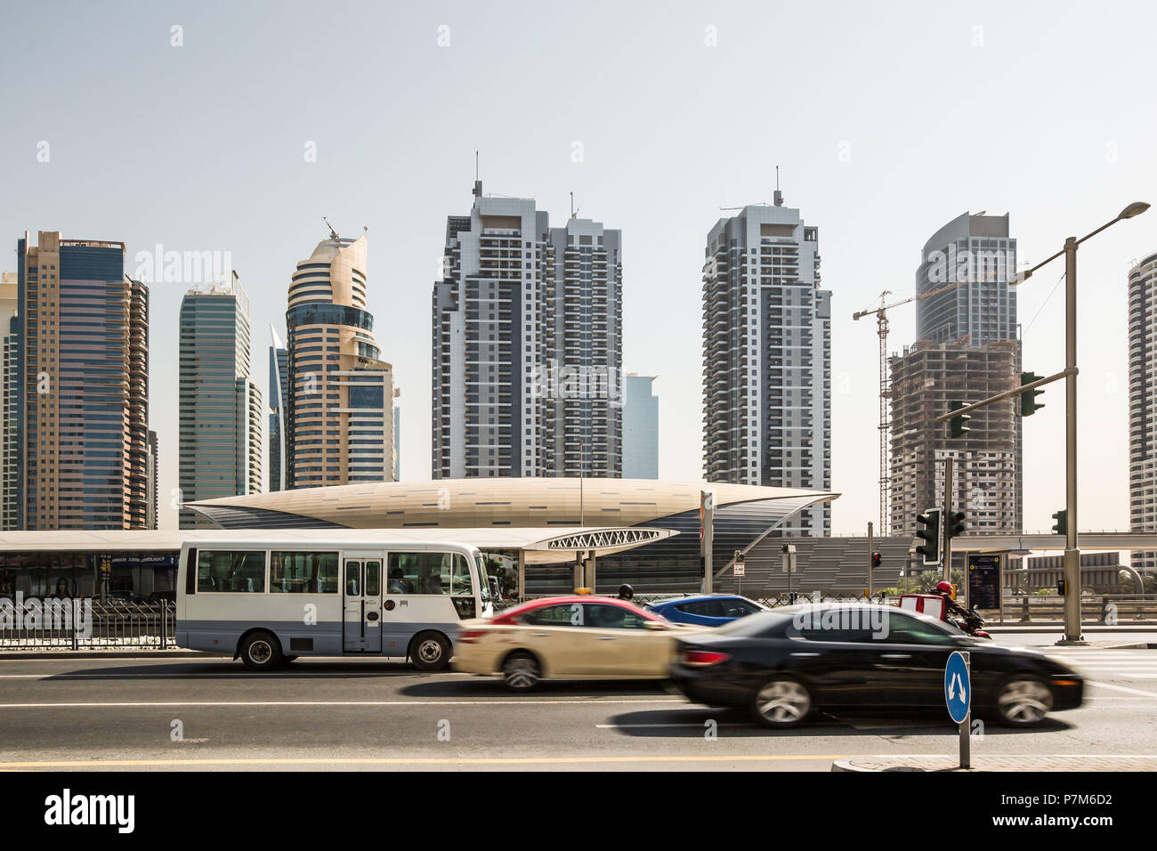 Cars on the street in front of futuristic building of Dubai metro station and modern skyscrapers in Dubai, United Arab Emirates - Stock Image
