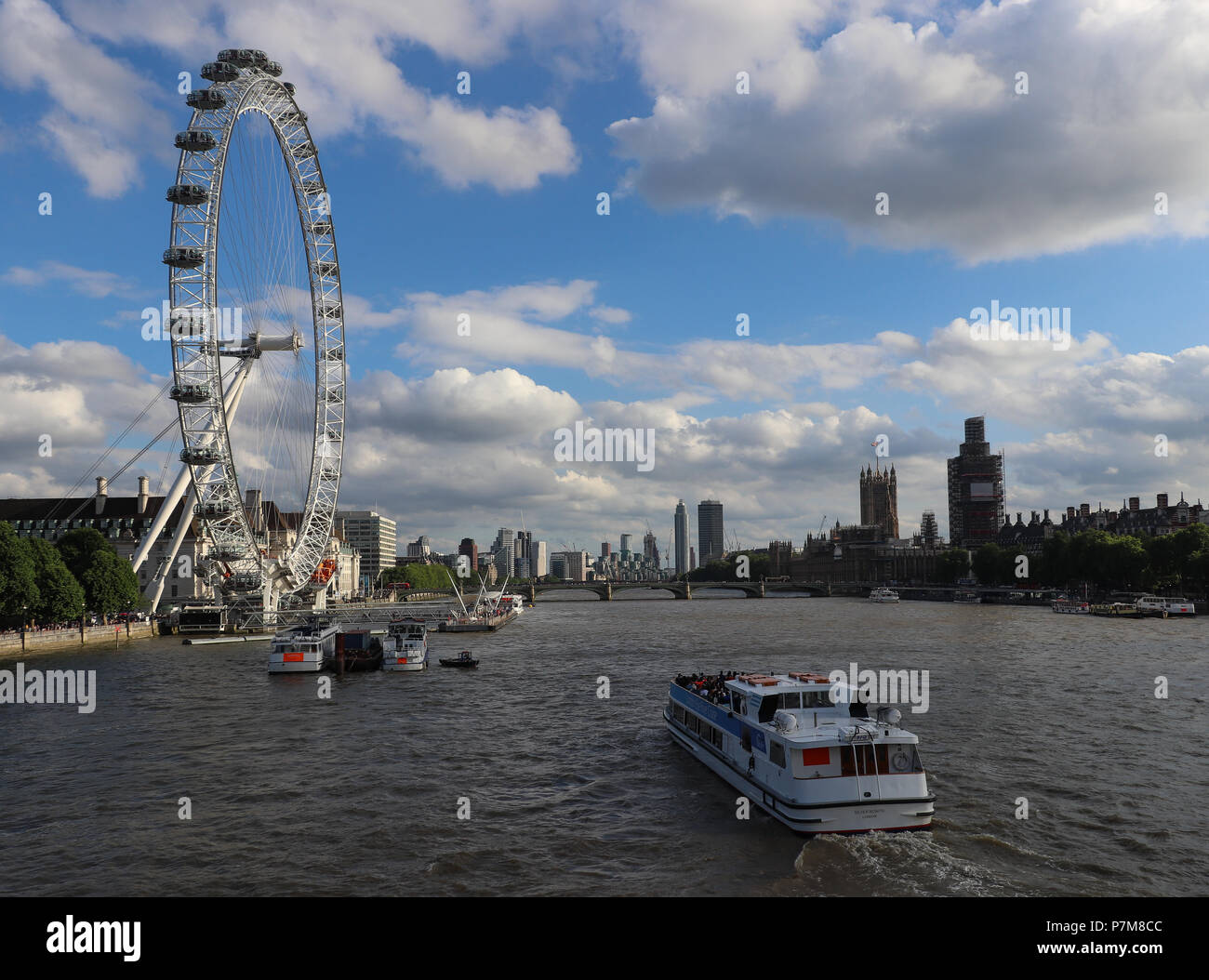 View down the River Thames of the London Eye and Houses of Parliament with scaffolding from the Hungerford Bridge; blue sky filled with white clouds - Stock Image