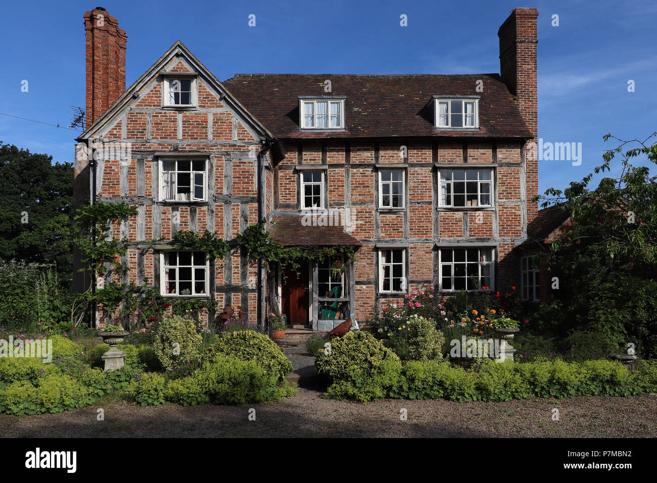 Lovely three story 17th C. country house in England constructed with brick infill on a timber frame, the timbers exposed, large chimneys, & wisteria Stock Photo