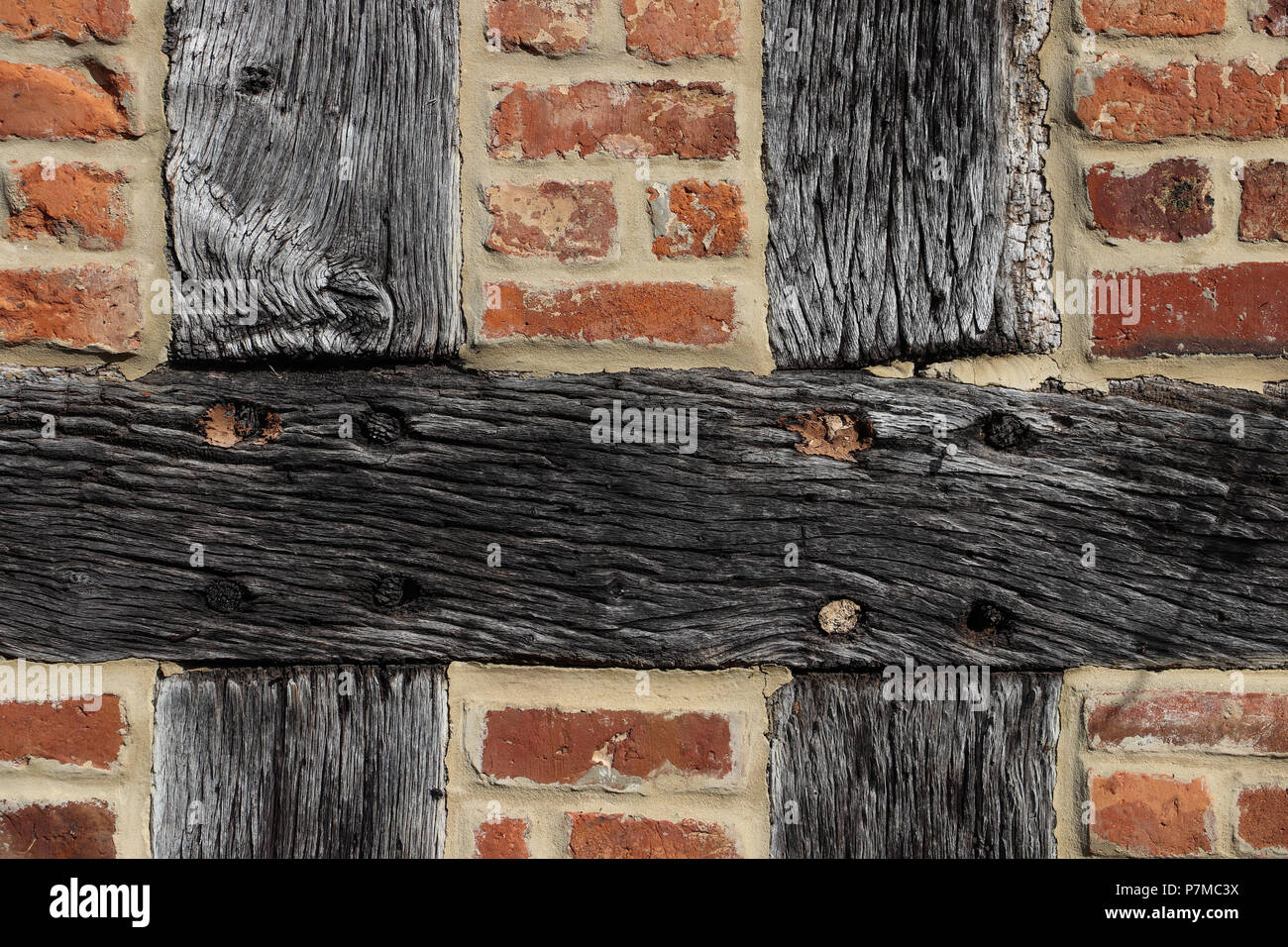 Closeup of the weathered timbers and brick infill on a 17th C timber-framed house;the timbers are held together by cross halving joint with wood pegs - Stock Image