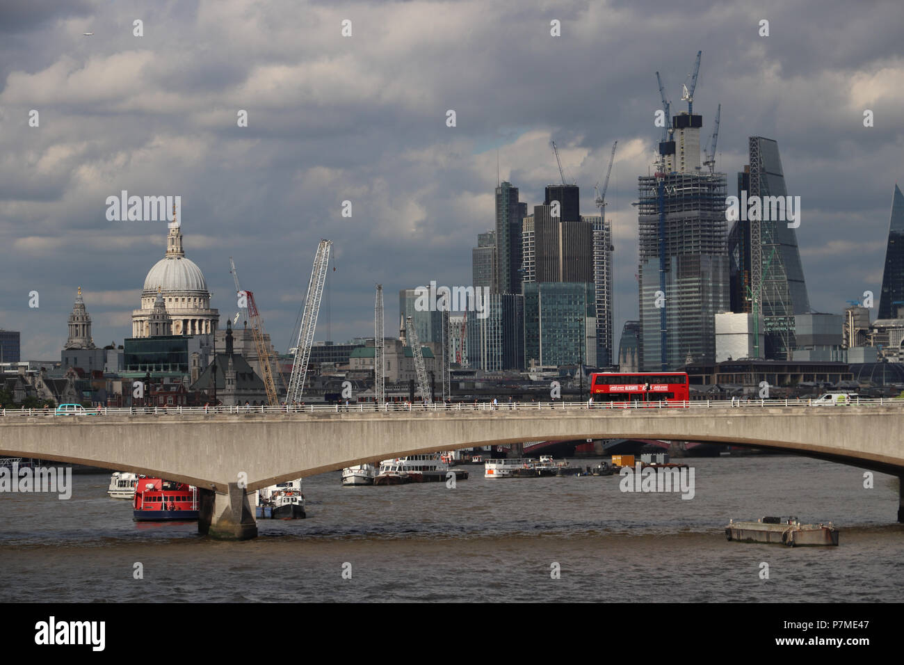 Panoramic view of London with red bus crossing the Waterloo Bridge  and St Paul's Cathedral sunlit, cluster of new skyscrapers in shadow of cloudy sky - Stock Image