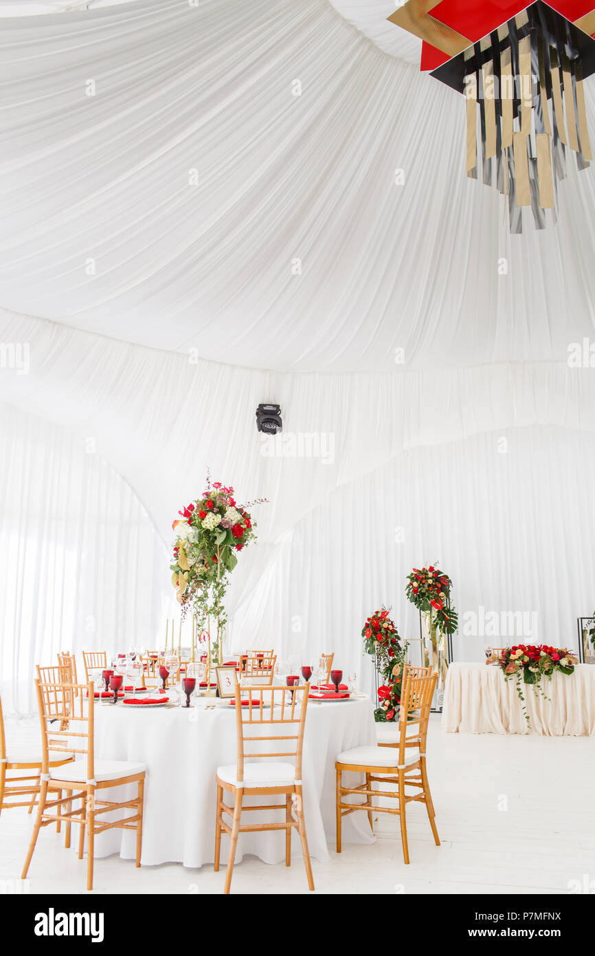 Beautiful banquet hall under a tent for a wedding reception. Interior of a wedding tent decoration ready for guests. Decor flowers. Red theme & Beautiful banquet hall under a tent for a wedding reception ...
